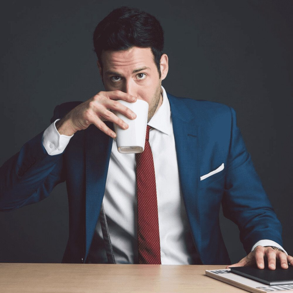 Writer and filmmaker Ari Frenkel takes a sip of a cup while wearing a suit.