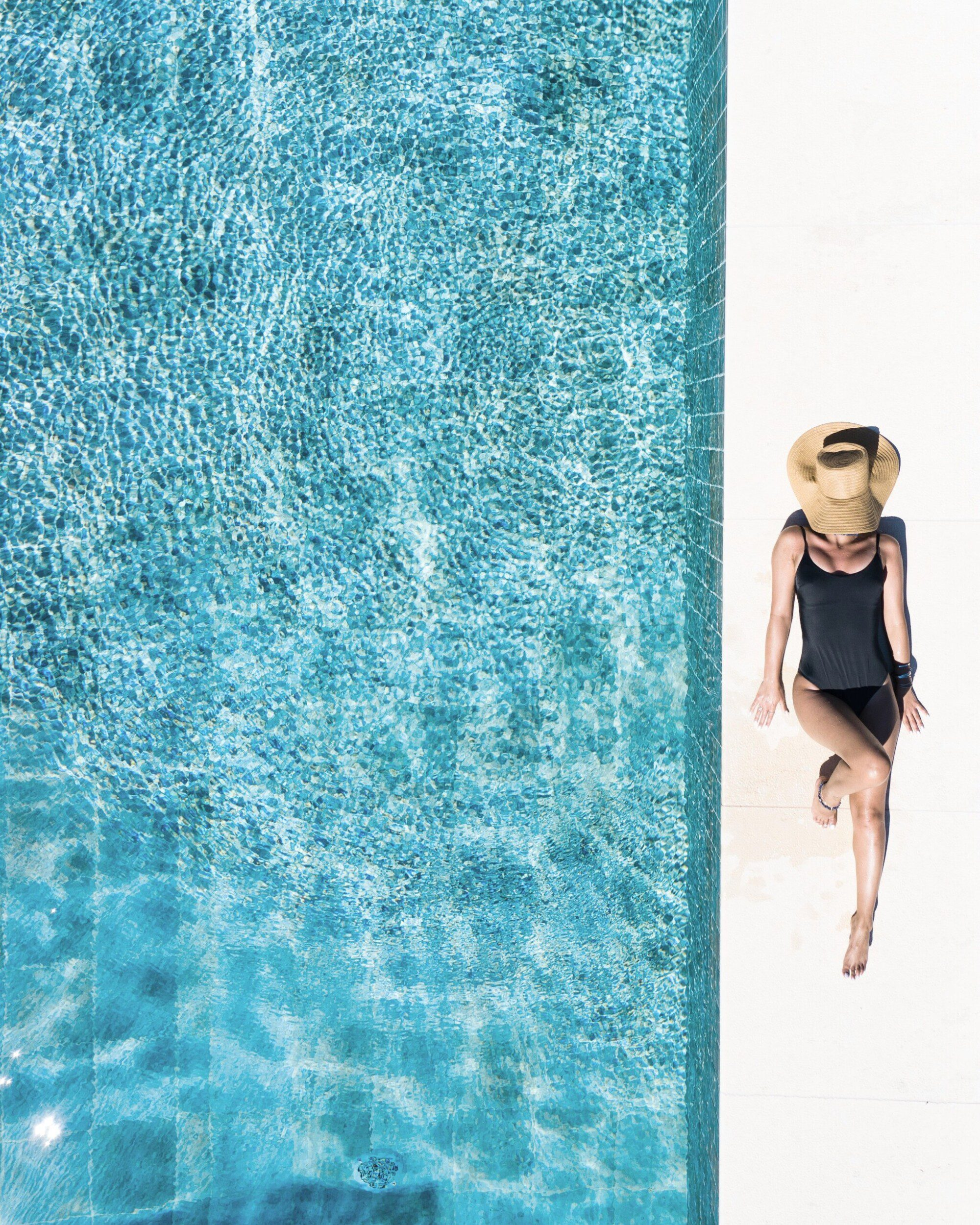 A woman relaxing laying at the edge of a sparkling blue pool.