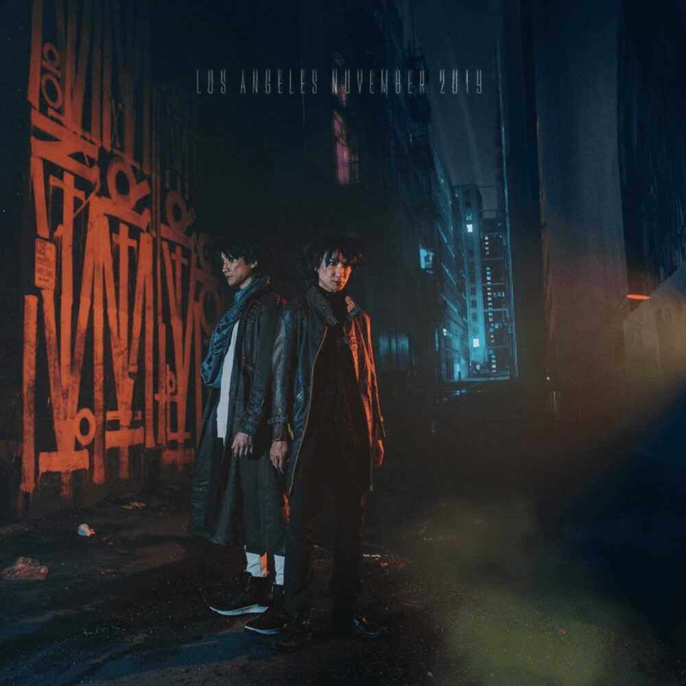Electronic pop duo Ming and Ping pose in a street at night.